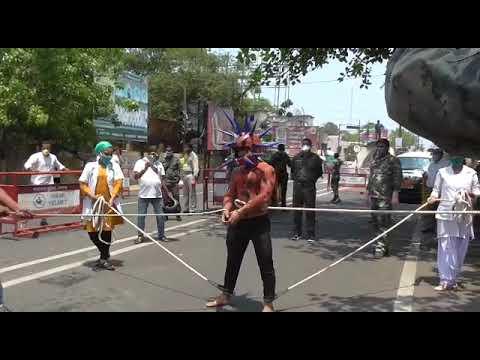 नुक्कड़ नाटक का दृश्य - रस्सियों से जकड़ाया कोरोना