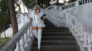 In White High-heeled Boots And A Mini-skirt In White Patent Fabric. I'm Walking In The Park.
