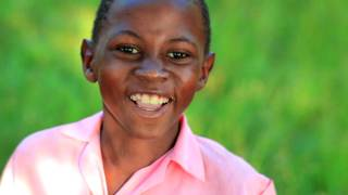 Little jumpy Kenyan boy smiling.