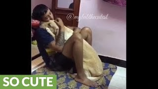 Dog cuddles with owner in the most heart-warming way possible!