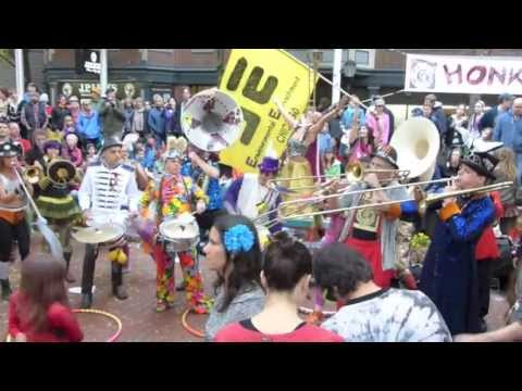 Mister Petey driving the EE Bomba, center with bass drum and purple hat, at HONK!Fest 2013 in Somerville MA