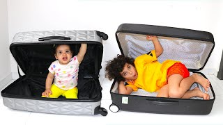 Sami and Amira pretend to play hide and seek with a suitcase