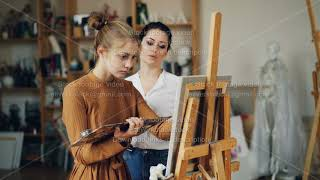 Experienced art teacher is working with pretty girl talanted student painting picture and talking