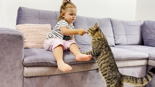 Cute Baby Feeds a Cat With Cat Treats