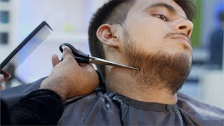 Shot of a barber trimming beard with scissors in a salon