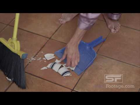 Barefoot woman cleaning up broken tea cup on floor