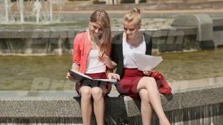 Two young college coeds learn together sitting by the fountain in the park. The sun is shining | Михаил Довидович