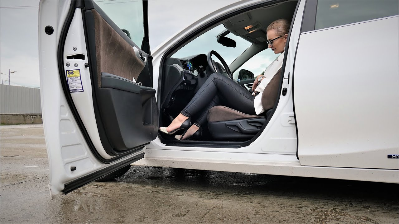 WOMAN DRIVING IN BLACK AND WHITE OUTFIT WITH HIGH HEELS
