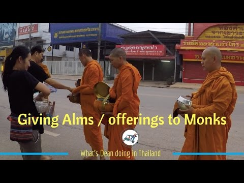 Giving Alms / offerings to Monks on the street in Thailand