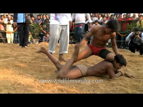 Indian kids compete at a mud wrestling in Delhi