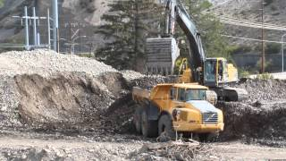 Volvo A40D Articulated Dump Truck dumping a load of rock and dirt then gettin filled up by an EC460B