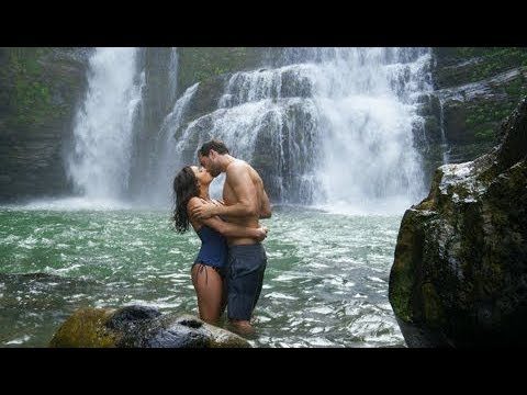 Romantic couple kissing in swimming hole near waterfall, stock video footage