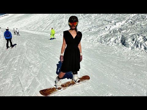 Красивая девушка зажигает на сноуборде в коктейльном платье