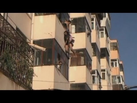 Couple rescued as they fall from balcony window