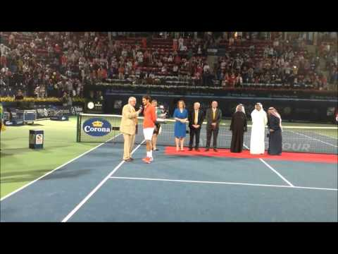 Roger Federer collecting trophy after winning the 2014 Dubai Duty Free Tennis Championships