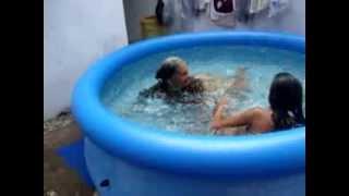 As crianças tomando banho de piscina