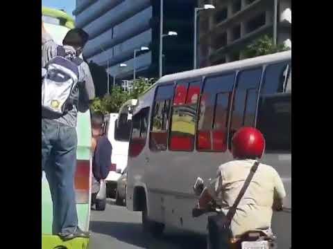 Pasajeros se cuelgan de los autobuses para poder llegar a sus trabajos