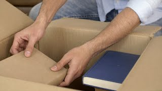 House relocation - Close-up shot of Indian man taking out books / novels from carton box