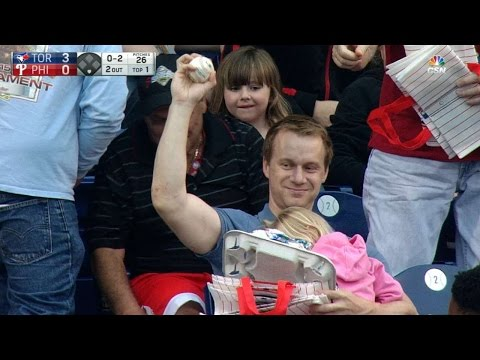 Fan grabs foul ball while holding his child