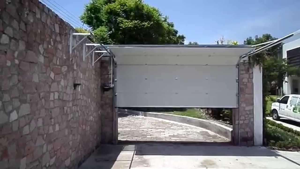 Puerta seccional sin marquesina automatizada con operador for Marquesinas para puertas