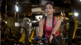 Beautiful Indian girl riding an exercise bicycle at the gym - cardio training concept