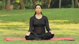 A young girl practicing sheetali / sheetkari pranayama outside in a park