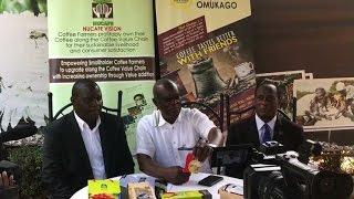 Hon. Gerald Ssendaula congragulates NUCAFE's Joseph Nkandu