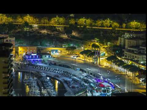 Cityscape of Monte Carlo, Monaco night timelapse with yachts and traffic on embankment