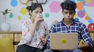 Indian girl telling her boyfriend to drink coffee while he is busy working on a laptop