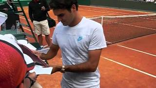 Roger Federer signs autograph after his training