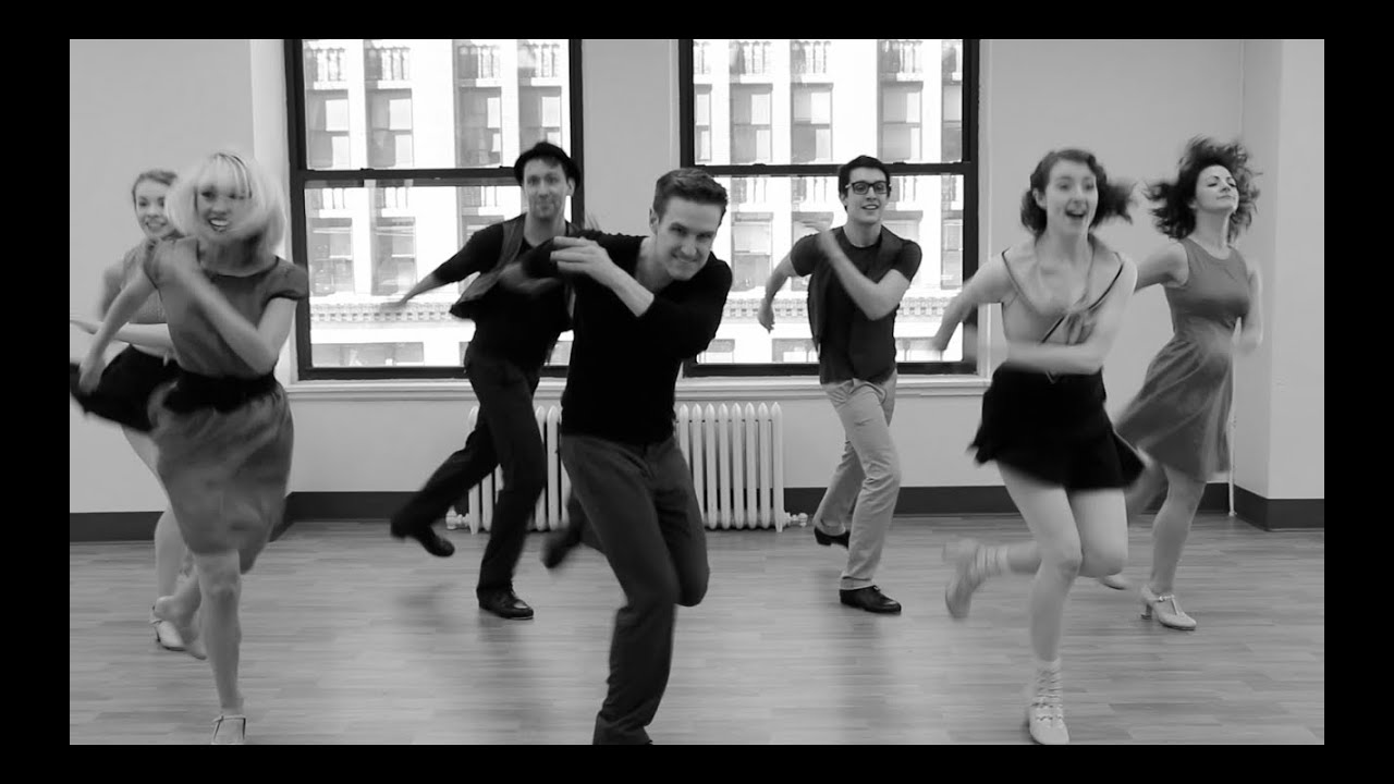 Black and white picture of people that are tap dancing in a class