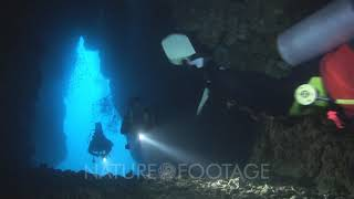 Scuba Divers Exploring Underwater Cavern By Flashlight At Western Rocky Island, Mergui Archipelag...