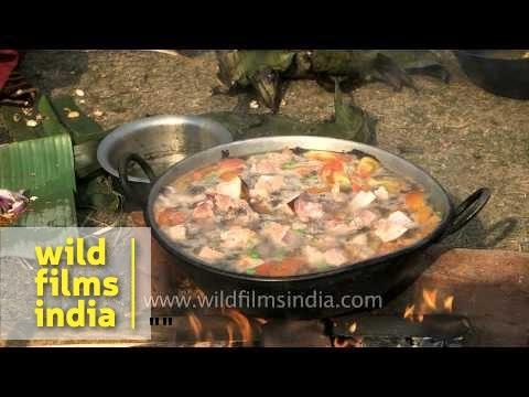 Tribal woman cooks pork dish - Jonbeel Mela, Assam