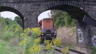 Pociąg z ponadgabarytowym ładunkiem ostrożnie przejeżdża pod wiaduktem i przy peronie.