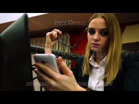 Business lady with glasses and smartphone in hand reading news, tense view