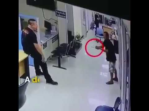 man enters bangkok police station with knife and is calmed by police officer