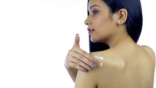 Back view of a young female applying cream on her shoulder - skincare concept