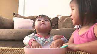 Cute baby and toddler fights over bowl of food