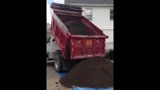 Dump truck dumping top soil