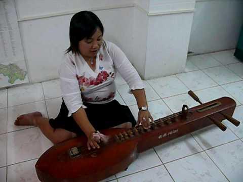 Thai lady playing Jakae Thai musical instrument 2 of 3