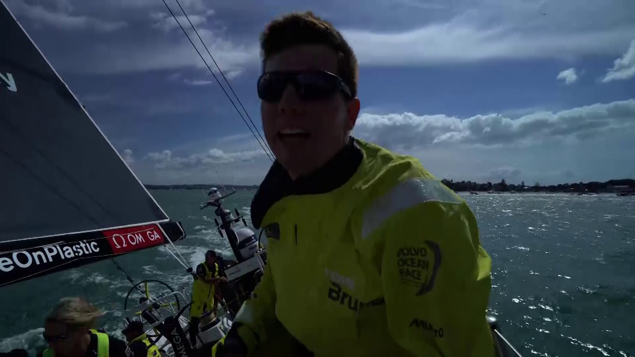 "Tacking out of Auckland harbor after the start. Bouwe is on the aft pedestal; Peter is on the helm. MAPFRE tacks ahead of the; they tack short. Then they converge on port with oncoming fleet on starboard: Scallywag, Vestas, TTToP, and then AkzoNobel still on port. Peter, steering from the leeaward wheel, calls: ""A little dip here."" We see them ducking Vestas and TTToP; MAPFRE and Dongfeng are visible ahead of them on port tack. Carlo calls the duck on the foredeck, then walks aft. Then we see Dongfeng crossing behind them under their A3 going downwind, then TTToP crossing behind them going upwind as Liz goes onto the foredeck. Carlo talks about how the start has been good. Then we see their jumper jump. Capey calling 5 minutes to the mark. Coiling lines in the pit. Bashing to weather on the foredeck."