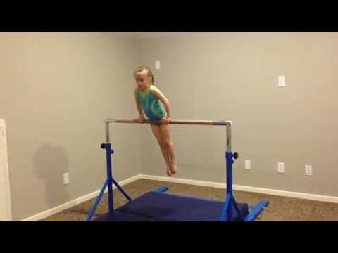 Taylor (6 years old) does a straddle cast handstand on the bar