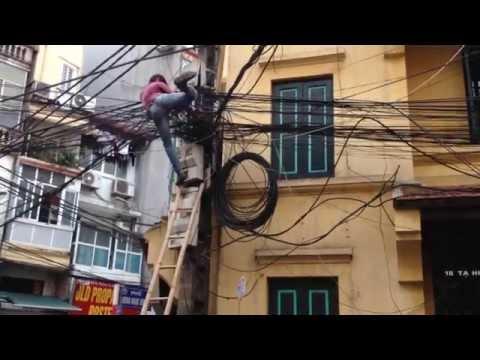 Vietnamese spiderman pulling cables in Hanoi, Vietnam