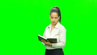 Cute girl dressed formally flipping the pages of a book and making gestures against the green screen
