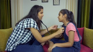 Young Indian siblings playing the role of doctor and patient at home - playtime