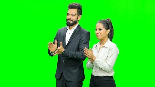 Boy and a girl dressed professionally standing against the chroma screen and clapping in appreciation