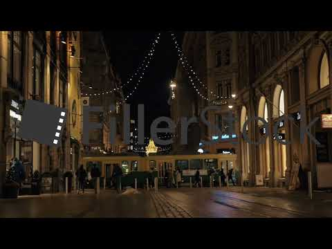 Walking people and passing tram in night street with Christmas lights, Helsinki