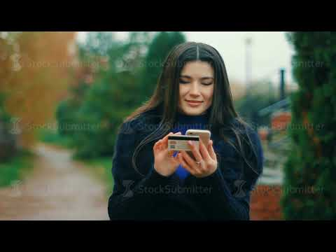 E-commerce concept - Brunette woman holding credit cards and smartphone make shopping