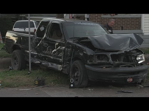Truck strikes parked vehicle, flips and hits house