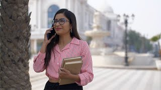 Beautiful Indian college girl happily talking to her best friend over a phone call